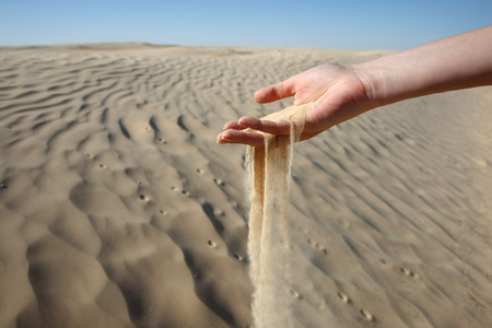 Sand slipping through the fingers of a woman photo