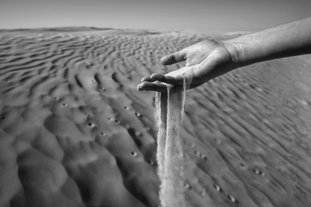 Sand slipping through the fingers of a woman Stock Photo