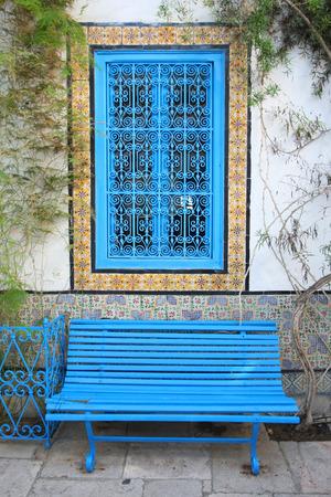 Blue panchina e finestra nel cortile di una tipica casa a Sidi Bou Said, Tunisia Sidi Bou Said � una citt� nel nord della Tunisia noto per l'uso di blu e bianco in esso