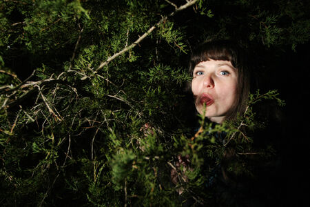 A young woman making grimace hiding in the trees  photo