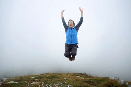 Un uomo diffondendo le mani e saltando sulla cima della montagna chiamata Grobnicke Alpe di Grobnik, Rijeka, Croazia Archivio Fotografico
