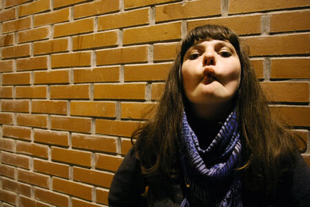 goofing: A young woman posing in front of a brick wall and goofing with her face