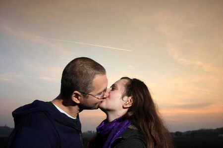 Young romantic couple with background of sunset,kissing and holding around each other  photo