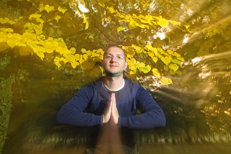 Casual dressed young man looking at camera with namaste greeting in autumn park  photo