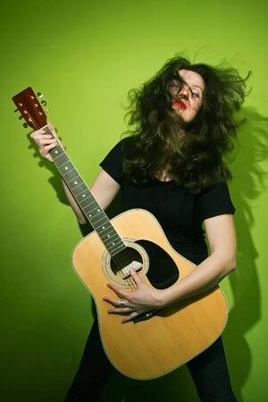 zerzaust: Portrait einer jungen Frau mit zerzausten Haaren spielt Gitarre auf gr�nem Hintergrund.