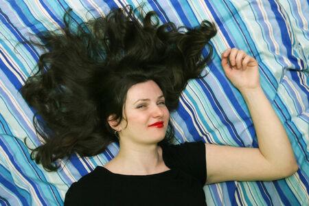 zerzaust: Eine Frau mit zerzausten Haaren liegen auf der Leinwand im Bett und schaut in die Kamera.