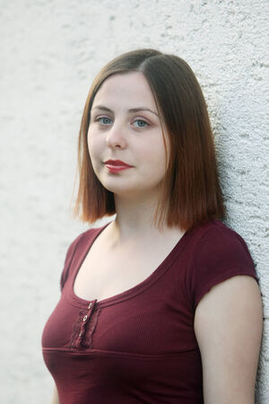 Young woman looking at the camera and posing in front of a white wall.