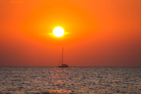 vibrat: A boat sailing on open sea at sunset  Stock Photo