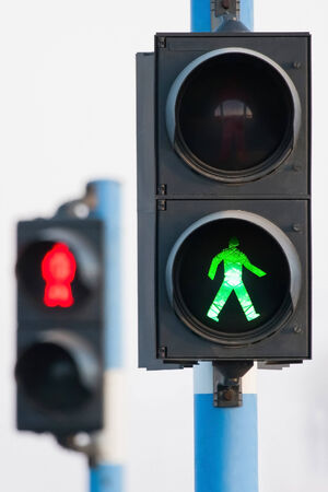 go sign: Traffic lights for pedestrians on two semaphores in traffic.
