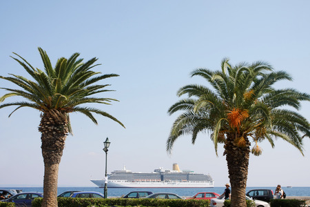 arcadia: ZAKYNTHOS - OCTOBER 4 : Palm trees on the Solomos Square with Arcadia Cruise Ship in the background on October 4, 2011 in Zakynthos, Greece. Editorial