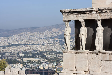 caryatids: The caryatids in the Erechtheion of Erechtheum, the ancient greek temple in the Acropolis of Athens with a view of the cityscape in Athens, Greece. Stock Photo
