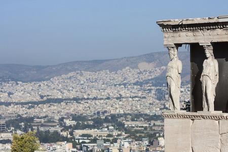 Le cariatidi dell'Eretteo di in Eretteo, tempio greco nella Acropoli di Atene, con una vista del paesaggio urbano di Atene, Grecia.