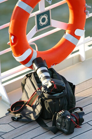 the next life: Camera bag on the cruise ship deck floor next to a fence with life jacket