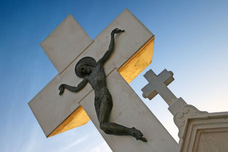 aslant: A stone statue of Jesus Christ crucifiied on cross at sunset.