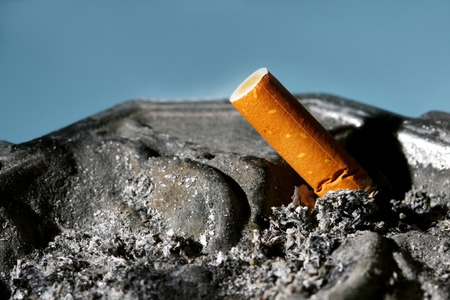 habbit: A close up of a cigarette butt in a metal ashtray on blue background.