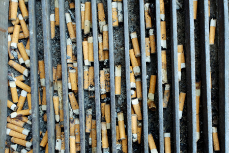 habbit: A close up of cigarette butts in a metal grid on the floor. Stock Photo