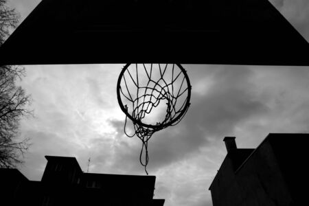 playground basketball: A silhouette of a basketball hoop at playground, taken from below