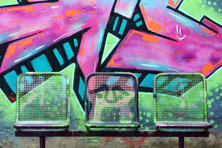 schoolyard: Three painted street chairs in front of graffiti wall on a schoolyard.