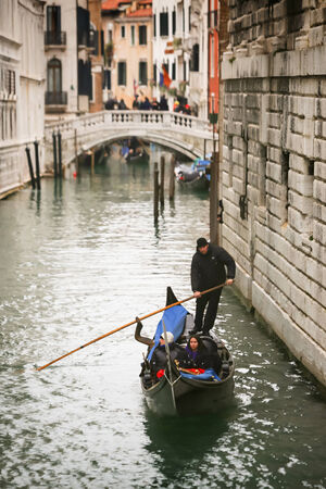 VENICE, ITALY - FEBRUARY 15 : A view of a gondola with tourists passing under The Bridge of Sighs (Ponto dei Sospiri) on February 15, 2014 in Venice, Italy. Ponto dei Sospiri passes over the Rio di Palazzo and connects the Doge Editorial