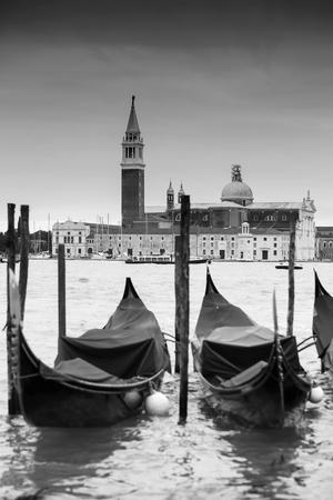 Una visione della Chiesa di San Giorgio Maggiore, sull'isola di San Giorgio Maggiore con gondole parcheggiate in acqua a Venezia, Italia.