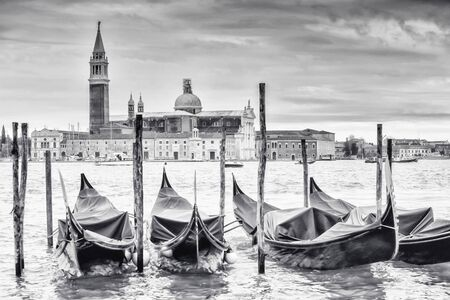 campanile: A view of the Church of San Giorgio Maggiore on the island of the San Giorgio Maggiore with gondolas parked in the water in Venice, Italy.