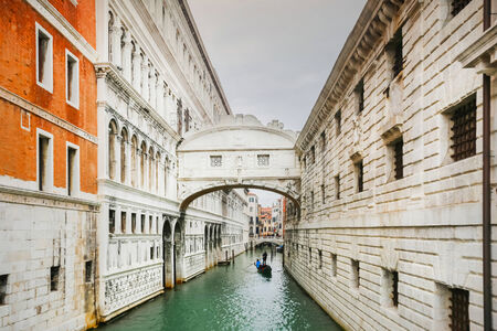 A view of a gondola passing under The Bridge of Sighs (Ponto dei Sospiri) in Venice, Italy. Ponto dei Sospiri passes over the Rio di Palazzo and connects the Doge Editorial