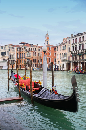 VENICE, ITALY - FEBRUARY 15 : A view of an empty gondola parked in a Campo Erberia square on grand canal with gondola with tourists passing behind it on February 15th, 2014 in Venice, Italy.