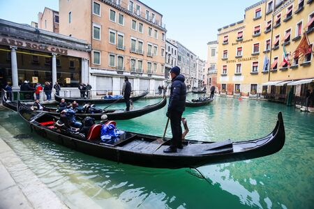 hard rock cafe: VENICE, ITALY - FEBRUARY 15 : Tourists and gondolas at a gondola station next to Hard rock cafe and Hotel Cavalletto on February 15th, 2014 in Venice, Italy.