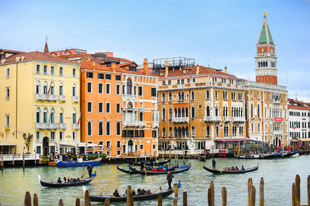 VENICE, ITALY - FEBRUARY 15 : Gondolas with tourists sailing through a grand canal with a view of the St Mark