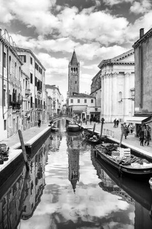 VENEZIA, ITALIA - 15 febbraio: Una vista di barche ormeggiate e vuoti allineati lungo i marciapiedi di un canale d'acqua con persone che camminano per la strada accanto a una chiesa di San Barnaba 15 febbraio 2014 a Venezia, Italia.