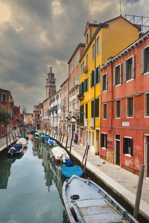 lined up: A view of empty boats moored and lined up along the sidewalks of a water canal in Venice, Italy.