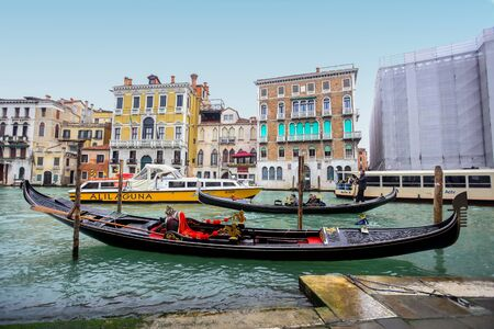 VENICE, ITALY - FEBRUARY 15 : A view of an empty gondola parked in a Campo Erberia square on grand canal with gondolas and boats with tourists passing behind it on February 15th, 2014 in Venice, Italy.