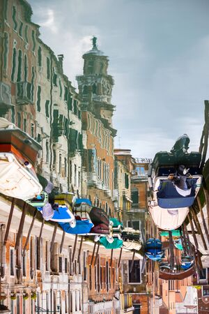 lined up: An abstract view of empty boats moored and lined up along the sidewalks of a water canal in Venice, Italy.