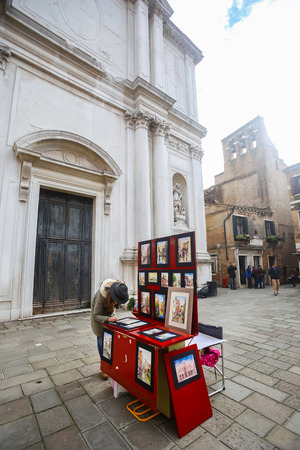 displayed: VENICE, ITALY - FEBRUARY 15 : A woman selling art pictures displayed at a stand in the street on February 15th, 2014 in Venice, Italy.