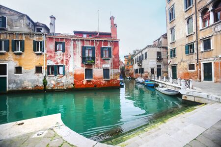 lined up: A view of empty boats moored and lined up along the sidewalk of a water canal in Venice, Italy. Stock Photo