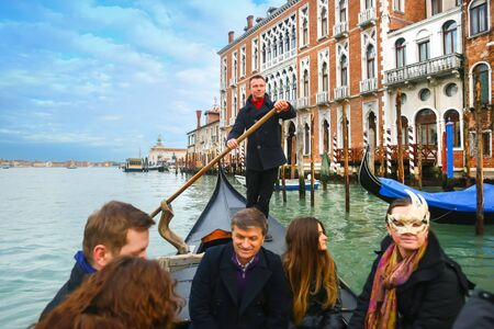 gondolier: VENICE, ITALY - FEBRUARY 15 : A front view of the inside of the gondola with gondolier and tourists sailing in the grand canal on February 15th, 2014 in Venice, Italy. Editorial