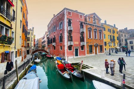 lined up: VENICE, ITALY - FEBRUARY 15 : A view of empty boats and gondolas moored and lined up along the sidewalks of a water canal with people passing by on February 15th, 2014 in Venice, Italy.