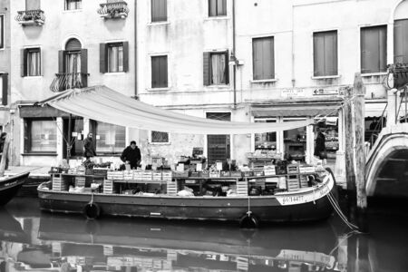 market place: VENICE, ITALY - FEBRUARY 15 : Fruit and vegetable market place on a boat in a water canal with people walking in the street on February 15th, 2014 in Venice, Italy. Editorial