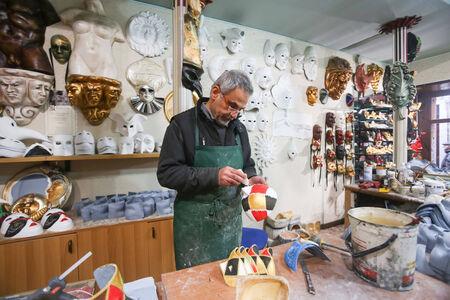 VENEZIA, ITALIA - 15 febbraio: Un artigiano che lavora su una maschera in un negozio di maschere il 15 febbraio 2014 a Venezia, Italia.