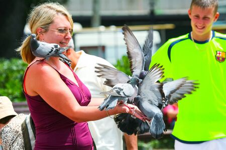 BARCELONA, SPAIN - JUNE 19 : A pigeons standing on the arm and shoulder of a woman that is feeding them on a town square on June 19th, 2006 in Barcelona, Spain.Feeding pigeons is a tourist attraction in Barcelona.