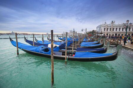 VENEZIA, ITALIA - 15 febbraio: Le gondole ormeggiate nel canale d'acqua di fronte a persone che camminano sulla Riva degli Schiavoni il 15 febbraio 2014 a Venezia, Italia.