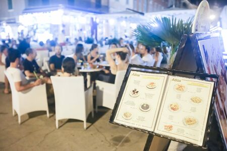 displayed: ROVINJ CROATIA  AUGUST 6 : A restaurant menu displayed on a stand with people sitting in a restaurant on the promenade at night on August 6th 2013 in Rovinj Croatia. Rovinj is a tourist destination on Adriatic coast of Croatia. Editorial