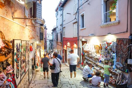 displayed: ROVINJ CROATIA  JULY 18 : People walking in the street next to souvenir shops and sightseeing the souvenirs displayed on the walls of the buildings on July 18th 2014 in Rovinj Croatia. Rovinj is a tourist destination on Adriatic coast of Croatia.