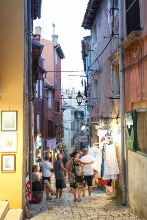 sightsee: ROVINJ CROATIA  JULY 18 : People walking in the street next to souvenir shops and sightseeing the souvenirs displayed on the walls of the buildings on July 18th 2014 in Rovinj Croatia. Rovinj is a tourist destination on Adriatic coast of Croatia.