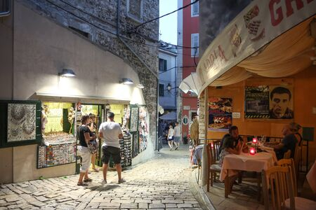 holiday lights display: ROVINJ CROATIA  JULY 18 : People walking in the street next to the souvenir shops and a restaurant on July 18th 2014 in Rovinj Croatia. Rovinj is a tourist destination on Adriatic coast of Croatia.