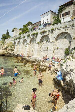 personas banandose: Rovinj CROACIA 20 de julio: Las personas que se ba�an en el baj�o y tomando el sol en las rocas de la playa de la ciudad el 20 de julio de 2014 en Rovinj Croacia. Rovinj es un popular destino tur�stico en la costa del Adri�tico, en Croacia.