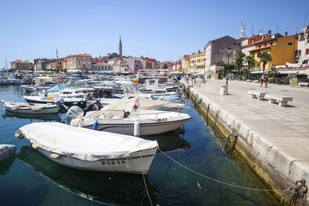 church group: ROVINJ CROATIA  AUGUST 3 : A large group of boats anchored in the marina with a view of the Saint Euphemia church and people walking on the city seafront on August 3rd 2013 in Rovinj Croatia.
