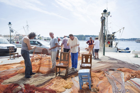 ROVINJ CROATIA  JULY 20 : Fishermen after fishing on the dock are stitching a driftnet connected to a moored fisher boat on July 20th 2014 in Rovinj Croatia.