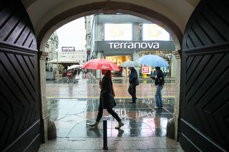 view through door: ZAGREB CROATIA  MAY 22 : A rainy and windy weather on the street of the city center on May 22 2015 in Zagreb Croatia. View through the door on the Ilica street with people walking in the rain with umbrellas.