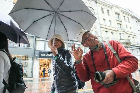 goofing: ZAGREB CROATIA  MAY 22 : A rainy and windy weather on the street of the city center on May 22 2015 in Zagreb Croatia. Funny tourists goofing and passing by in a rain in the Ilica street.